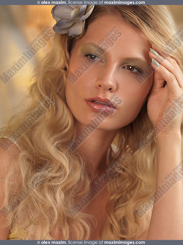 Portrait of a beautiful young woman with a flower in her blond hair