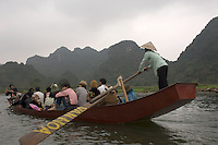 A boatload of pilgrims are rowed up the River Yen on their way to the Perfume Pagoda during the annual Tet festival in Vietnam.