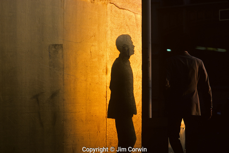 Silhouetted man along downtown street at sunset shadow on wall turning corner to cross street Seattle Washington State USA
