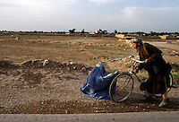 A man stops to give money to a woman on the side of the road towards Mazar-i-Sharif. <br /> <br /> Sheberghan, Jowzjan Province.