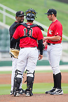 Kannapolis Intimidators pitching coach Jose Bautista (38) had a meeting on the mound with catcher Omar Narvaez (10) and pitcher Dylan Chavez (29) during the South Atlantic League game against the Greenville Drive at CMC-Northeast Stadium on April 6, 2014 in Kannapolis, North Carolina.  The Intimidators defeated the Drive 8-5.  (Brian Westerholt/Four Seam Images)