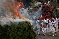 Yamabushi or mountain priests carry mikoshi made of arrows through the smoke of a large bonfire during the Hi Watari firewalking festival, Takaosan guchi near Tokyo, Japan. Sunday March 8th 2009