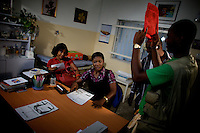 """Actress Biola Ige, ( on left ) reviews her part while  """"2009 African Movie Academy Award"""" winner for best performance by an actress  in a supporting role Mercy Johnson ( on right sitting down )  gets ready to play  her part during the filming of """"The Darkest Link"""", a Nollywood production, in Lagos, Nigeria on Thursday April 2 2009...Currently, Nigerian films outsell Hollywood films in Nigeria and many other African countries..Nollywood is a nascent film industry in Nigeria, growing up within the last two decades to become the third largest film industry on the planet, behind the United States and Indian film industries. Nigeria has a US$250 million movie industry, churning out some 200 videos for the home video market every month."""