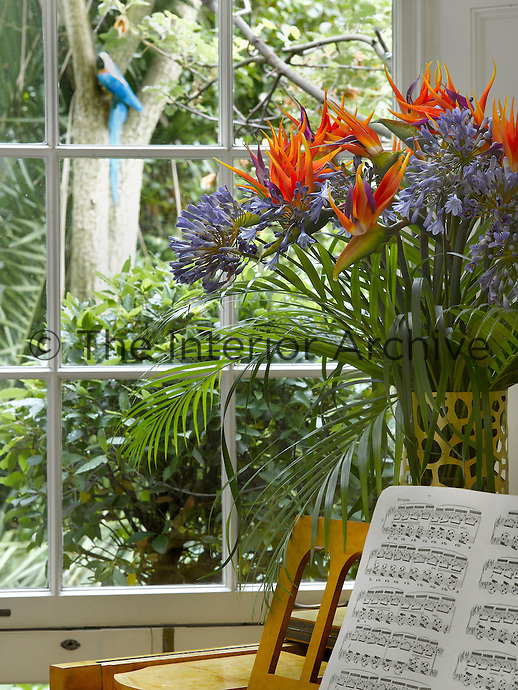 Detail of a vase of Agapanthus on top of the piano in the living room
