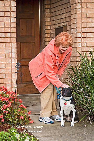 Senior red headed woman pets her black and white dog on the head in front of her house