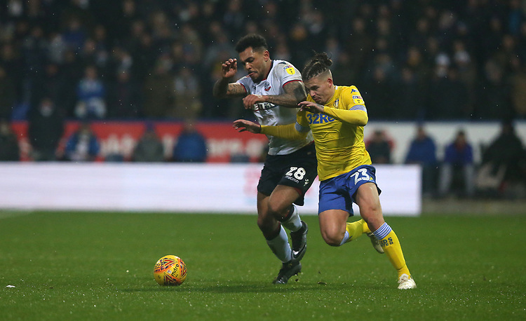 Leeds United's Kalvin Phillips chased by Bolton Wanderers' Josh Magennis<br /> <br /> Photographer Stephen White/CameraSport<br /> <br /> The EFL Sky Bet Championship - Bolton Wanderers v Leeds United - Saturday 15th December 2018 - University of Bolton Stadium - Bolton<br /> <br /> World Copyright © 2018 CameraSport. All rights reserved. 43 Linden Ave. Countesthorpe. Leicester. England. LE8 5PG - Tel: +44 (0) 116 277 4147 - admin@camerasport.com - www.camerasport.com