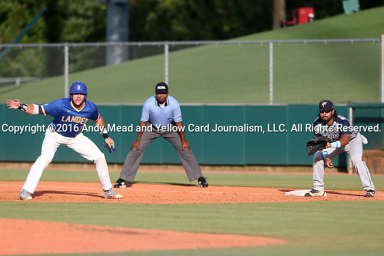 31 May 2016: Lander's Colby Lusignan (left) tries to distract the pitcher (not pictured) while taking a lead off of first base, guarded by Nova Southeastern's Andres Visbal (right). The Nova Southeastern University Sharks played the Lander University Bearcats in Game 8 of the 2016 NCAA Division II College World Series  at Coleman Field at the USA Baseball National Training Complex in Cary, North Carolina. Nova Southeastern won the game 12-1.