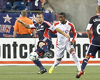 New England Revolution substitute forward Chad Barrett (9) attempts to control the ball as Toronto FC substitute midfielder Jeremy Hall (25) defends. In a Major League Soccer (MLS) match, Toronto FC (white/red) defeated the New England Revolution (blue), 1-0, at Gillette Stadium on August 4, 2013.