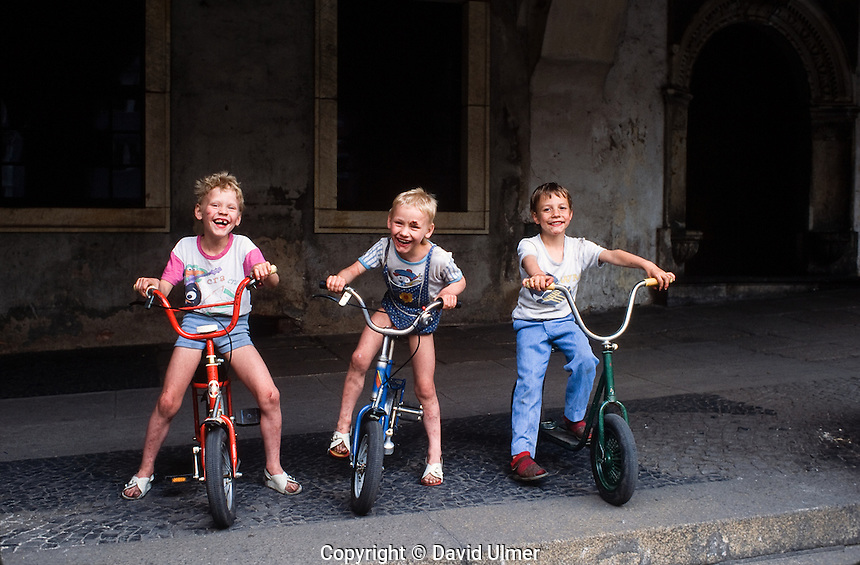 Three happy, dirty, young boys on bikes.  Gorlitz, East Germany 1990
