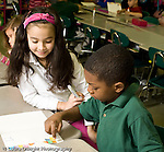 Education Elementary school Grade 1 mathematics hands on learning boy and girl using colored squares to understand concept gluing them to paper counting squares horizontal