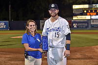 Asheville Tourists creative marketing manager Sam Fischer presents first baseman Brian Mundell (15) his league MVP award after a game against the Hagerstown Suns at McCormick Field on September 4, 2016 in Asheville, North Carolina. The Suns defeated the Tourists 10-5. (Tony Farlow/Four Seam Images)