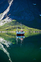 Reflection of moored boat against cliff, Vindstad, Moskenesoy, Lofoten islands, Norway