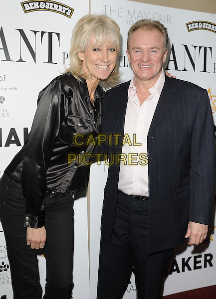 GUEST & BOBBY DAVRO .At the Joshua Foundation Gala Fundraiser, May Fair Hotel, London, England, UK, April 16th 2011..half length black shirt jeans navy blue arm around smiling  pinstripe suit .CAP/CAN.©Can Nguyen/Capital Pictures.