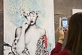 27 February 2014, London, United Kingdom. Pictured: A young woman takes a picture of the painting of a young woman entitled Hush 2014. The Art14 Art Fair at Olympia Grand Hall, London, opens its doors to the public from 28 February to 2 March 2014. Art14 London features 180 galleries from 40 countries with works from emerging talents to modern masters.