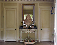 The entrance hall is a perfectly proportioned square with painted panelled walls and a pair of identical doors on either side of the console table
