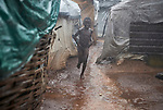 A boy runs in the rain through a displaced persons camp at the Holy Family Catholic Church in Wau, South Sudan. The church has provided food, shelter material, and health care, and the presence of clergy and religious has fostered a sense of relative safety for the families who first occupied the church grounds when fighting enveloped the city in 2016.