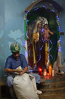 A miner and the Lady of the Miners in a gallery  under ground in a gold mine near Segovia, Antioquia department, Colomb ia