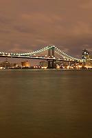 Manhattan Bridge and East River Illuminated at Night, showing lights of subway train crossing the bridge, New York City, New York State, USA