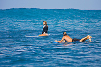 Surfer couples, enjoying riding rare big ocean waves in Kona Coast, Keauhou Bay, Big Island, Hawaii, Pacific Ocean.