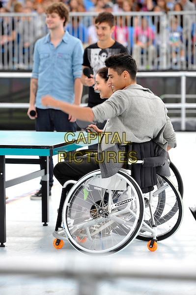 The Wanted - Jay McGuiness, Tom Parker & Siva Kaneswaran.London - Members of boyband 'The Wanted' play 'wheelchair table tennis' as part of the Sainsburys Super Saturday. The event raises funds for the Paralympic Legacy Fund and celebrates one year to go until the Paralympic Games.  London, England..September 10th 2011.band group sitting sitting jeans denim profile side  table sport paddle  ping pong arm in air blue grey gray jacket.CAP/ROS.©Steve Ross/Capital Pictures