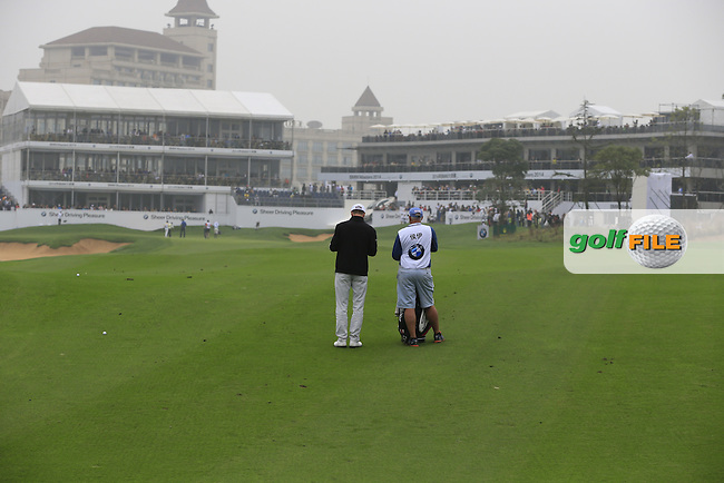 Michael Hoey (NIR) and caddy Gerry wait on the 18th hole during Saturay's Round 3 of the 2014 BMW Masters held at Lake Malaren, Shanghai, China. 1st November 2014.<br /> Picture: Eoin Clarke www.golffile.ie