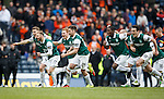 Hibs players race down to greet their keeper after winning the penalty shootout