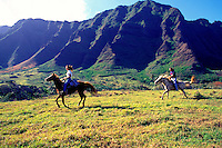 A couple on horses gallop across a grassy meadow at Kualoa Ranch on Oahu. The beautiful lushly sculpted Koolau mountains rise in the background.