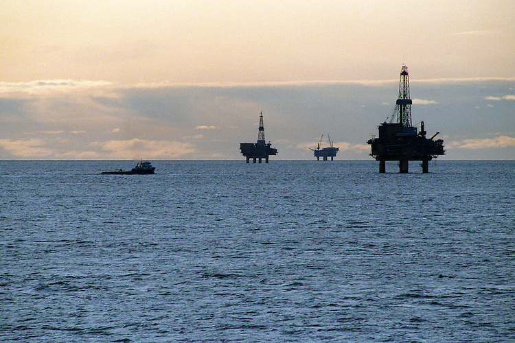 Oil industry platforms stand in Cook Inlet, offshore from Nikiski, Alaska, as a spill response and service vessel idles nearby. Oil and natural gas are an important contributor to the Kenai Peninsula's economy.
