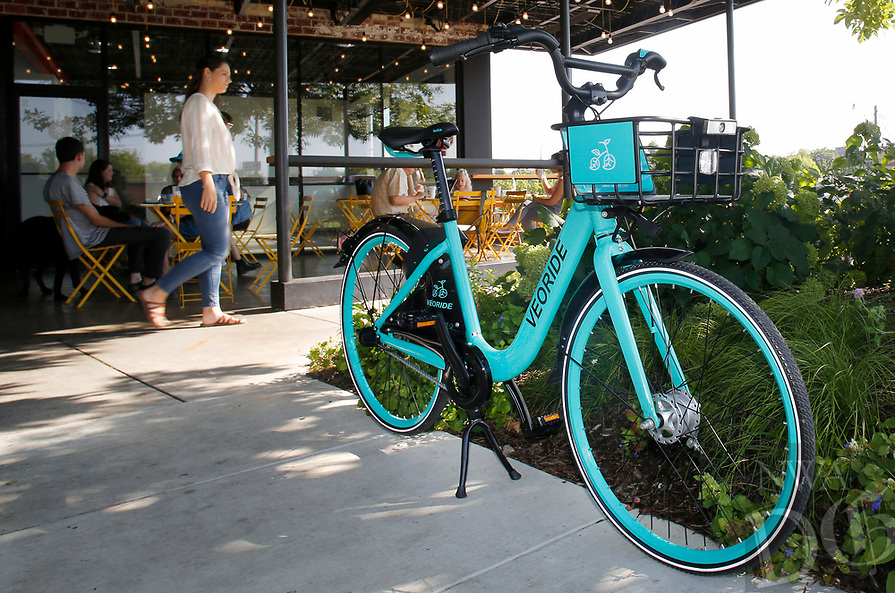 NWA Democrat-Gazette/DAVID GOTTSCHALK A demonstration bike for the new bike-share program in the city is parked Friday, August 3, 2018, in front of the Arsaga's Church & Center in Fayetteville. The city of Fayetteville, University of Arkansas, Fayetteville and Experience Fayetteville teamed up to bring the program for the bikes that will be red and white with signage.