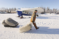 February 16, 2013  Volunteer John Hooley slides 3 bales of hay toward an airplane headed to Rainy Pass at the Willow airport as musher food, straw, HEET and people food is flown to the 4 checkpoints on the east side the Alaska Range. ..Photo Copyright Jeff Schultz  -- Do not reproduce without written permission