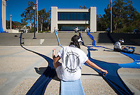 "Back of the uniform worm by volunteers with the Knitting Nation logo. Photo of textile artist, fashion designer and Wanlass Artist-in-Residence Liz Collins' work, ""Knitting Nation Phase 12: H2O"" as it was created at Occidental College on November 6, 2013. Knitters, many of them Oxy students, used 450 pounds of yarn as part of the day-long performance art piece on the steps of Johnson and Fowler Halls and AGC Administrative Center. (Photo by Marc Campos, Occidental College Photographer)"