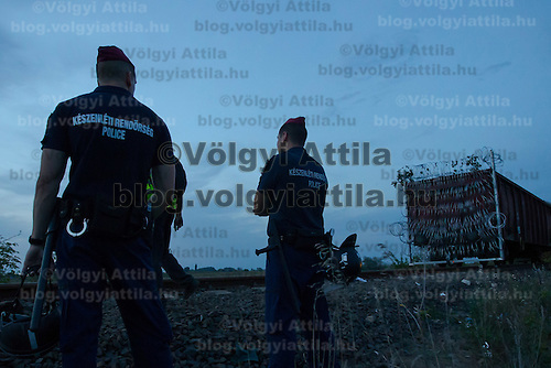 Police officers watch as a train mounted section is taken to the border on the railway to close down the last few meters of the fence on the border between Serbia and Hungary near Roszke (about 174 km South of capital city Budapest), Hungary on September 14, 2015. ATTILA VOLGYI