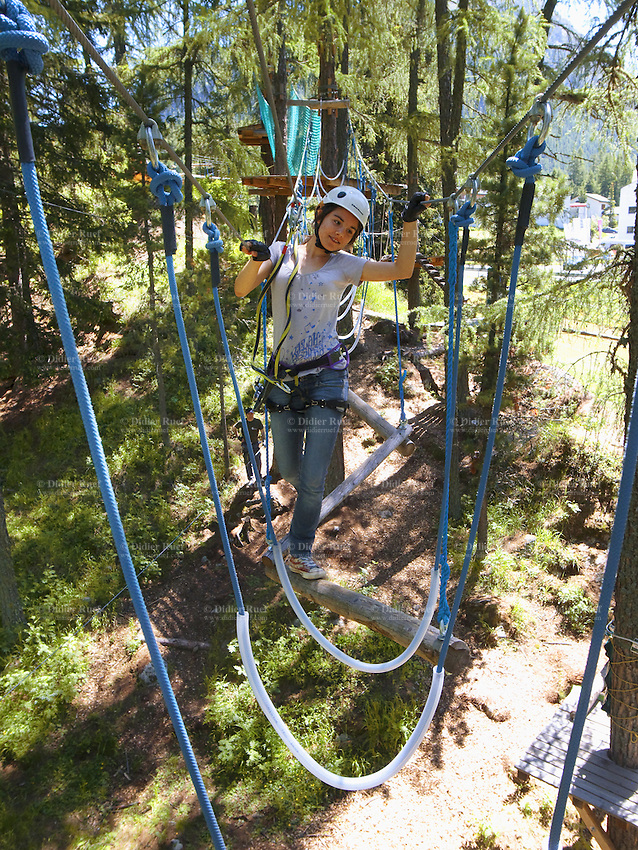 Switzerland. Canton Graubunden. Pontresina. Tree adventure. Micaela Ruef is taking an adventure in the forest by walking on a wood brench and using a wire from tree to tree as a security measure. Wearing a helmet and a harness and attached to wheel system that allows her to glide down the zip line. 26.06.11 MODEL RELEASED © 2011 Didier Ruef..