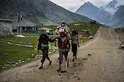 Porters carry a hindu pilgrim on the pallanquin along the Amarnath trekking route in Panchtarni in Kashmir, India. Hindu pilgrims brave sub zero temperature and high latitude passes and make their pilgrimage to reach the sacred Amarnath cave, which houses a lingam - a stylized phallus, worshiped by Hindus as a symbol of God Shiva. Photo: Sanjit Das/Panos