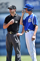 Asheville Tourists bat boy Bryce Ballew shares a drink with umpire Jason Johnson during a game against the Charleston RiverDogs at McCormick Field on July 10, 2016 in Asheville, North Carolina. The Tourists defeated the RiverDogs 4-2. (Tony Farlow/Four Seam Images)