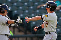 Salt Lake Bees outfielder Peter Bourjos (17) is greeted by teammate Luis Rodriguez after scoring in the first inning of the Pacific Coast League baseball game against the Round Rock Express on August 10, 2013 at the Dell Diamond in Round Rock, Texas. Round Rock defeated Salt Lake 9-6. (Andrew Woolley/Four Seam Images)