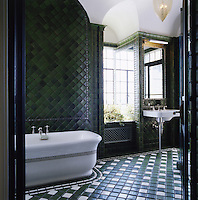 The geometric design of the tiling in this elegant green and white bathroom is reminiscent of North Africa