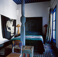 In the white and blue bedroom, two Moroccan babouche-makers' workbenches serve as bedside tables. On the wall is a tobe from Nigeria, a Peul wedding hanging and photographs by Paul Biehn and Hans Sylvester.