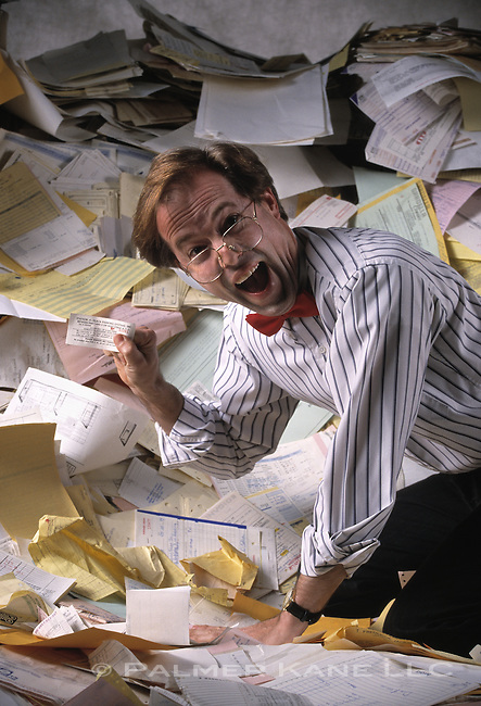 Executive in a paper pile finding receipt