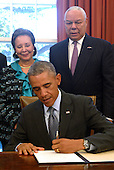 United States President Barack Obama, with America's Promise Alliance Founding Chairman and former US Secretary of State General Colin Powell (R) and current Board Chair Alma Powell (L), signs the America's Promise Summit Declaration during a ceremony in the Oval Office of the White House in Washington, DC, USA 22 September 2014. President Obama will be the seventh consecutive president to sign the declaration, which calls on Americans to help the youth of America reach their full potential.<br /> Credit: Shawn Thew / Pool via CNP