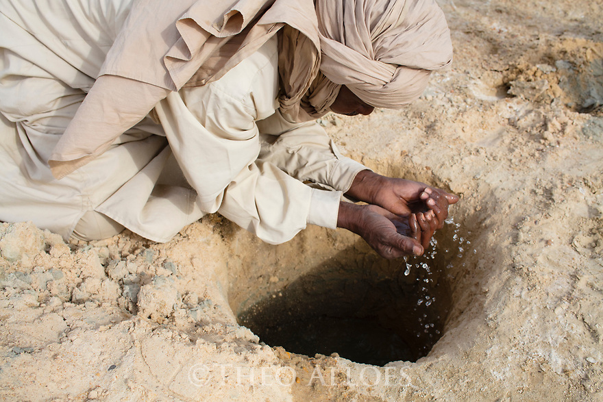 Chad (Tchad), North Africa, Sahara, Borkou District, Chad man drinking fresh water out of a hole in salt pan