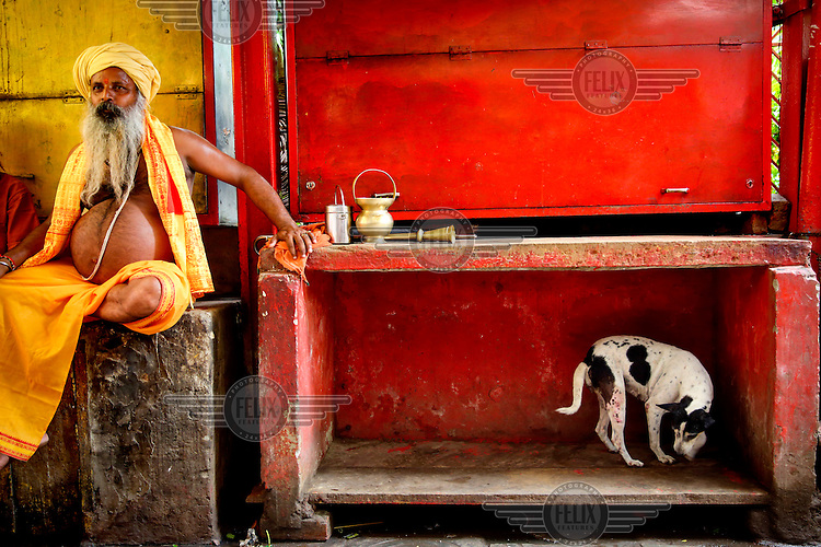 A portly sadhu sits cross legged near a dog.
