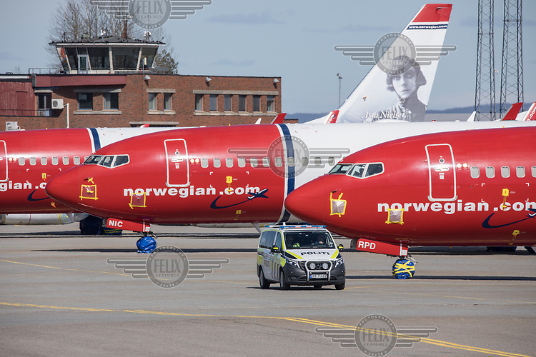 """A police car drives on the tarmac in front of aircraft """"mothballed"""" as they are grounded due to the coronoa crisis. <br /> <br /> Norwegian authorites introduced measures to combat the Coronavirus (COVID-19)  leaving Gardermoen Airport, near the Norwegian capital Oslo, deserted. <br /> <br /> Restriction on public gatherings and travel have grounded most airplanes, and stopped nearly all domestic and foreign travel. <br /> <br />  Like most capitals, Oslo is usually busy on a Saturday night. But on the first weekend after Norwegian authorites introduced measures to combat the Coronavirus (COVID-19) the city was almost deserted. <br /> <br /> Restriction on public gatherings, closure of schhols, new rules for those serving food and drinks, and fear of further spread of the virus compelled most bars and restaurants to close. <br /> <br /> 28,5 million passangers used the airport in 2018, with the airline Norwegian flying the most people. At teh time of writing Norweigan is on the verge of bankruptcy, and hoping to get governemnt aid to surive the economic crisis caused by the corona virus.  <br /> <br /> <br /> ©Fredrik Naumann/Felix Features"""