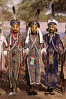 Akadaney, Niger, Africa - Fulani Wodaabe Dancers at Geerewol.  Participants in what westerners often call the male beauty contest, in which the whiteness of the eyes and the teeth is an important factor in appealing to the female spectators.  The dancers in the middle and on the right are wearing leather wallets, the red and green pouches hanging around the neck from a cord.
