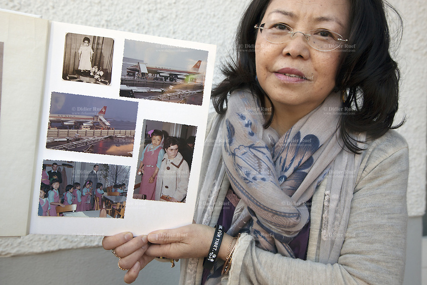 Switzerland. Canton Aargau. Rüfenah. Yangchen Büchli at home with the photo album of her arrival on board a Swissair flight in Zürich-Kloten airport on march 16, 1964. The swiss tibetan woman is an Aeschimann's child who arrived 50 years ago in Switzerland to receive custody on a private initiative by an influential Swiss industrialist, Charles Aeschimann. In 1962, Charles Aeschimann agreed with the Dalai Lama to take 200 children and place them in Swiss foster homes and give them a chance for a better life and a good education. Most of the children still had parents in exile or in Tibet, just a few were orphans. On the left bottom corner, Charles Aeschimann with the tibetan chiildren. 25.02.2015 © 2015 Didier Ruef