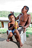 BELIZE, Punta Gorda, Village of San Pedro Colombia, Eladio Pop at his home with one of his 15 children holding a Cacao pod