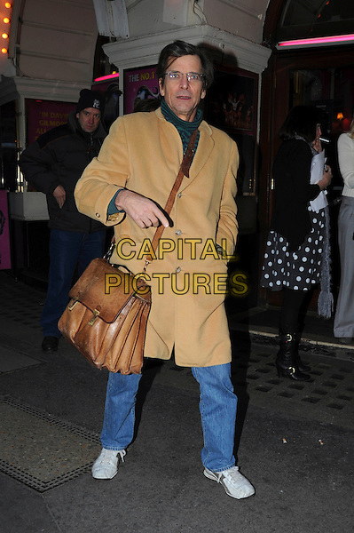"DIRK BENEDICT .Leaving after a performance of ""Grease"" the musical, Piccadilly Theatre, London, England, UK, 26th November 2010..full length brown bag satchel camel yellow coat hand jeans polo neck green striped glasses.CAP/IA.©Ian Allis/Capital Pictures."