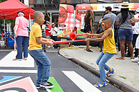 Two young brothers having a tug of war with long plastic horns.