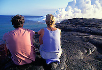 Spectators watching lava flow into the ocean at Hawaii volcanoes national park.