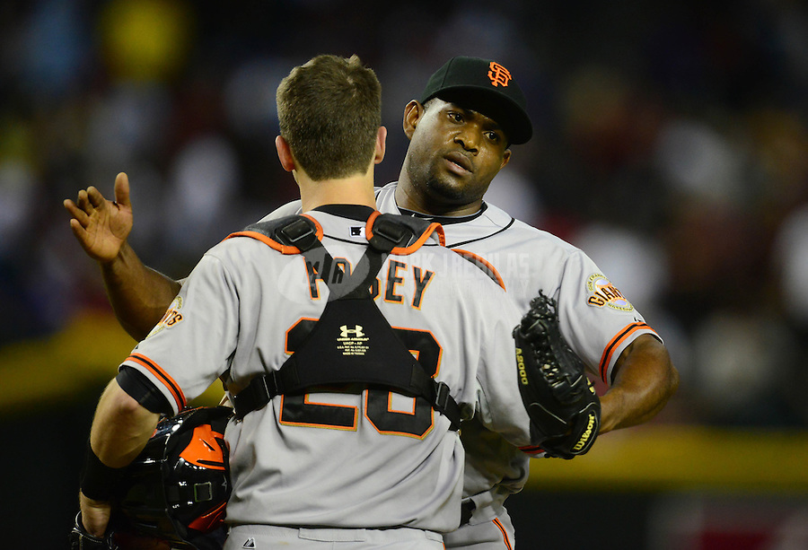 May 12, 2012; Phoenix, AZ, USA; San Francisco Giants pitcher Santiago Casilla (right) celebrates with catcher Buster Posey following the game against the Arizona Diamondbacks at Chase Field. Mandatory Credit: Mark J. Rebilas-